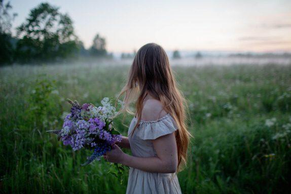 Nainen niityllä kädessään kukkia