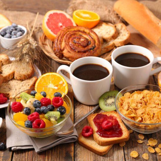 Kuvassa aamiaispöytä kaksi kahvikuppia hedelmiä marjoja muroja leipää ja pulla.