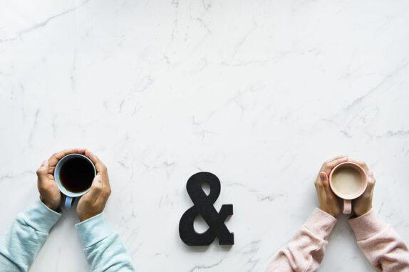 Kahvikuppeja ihmisten käsissä ja välissä & merkki