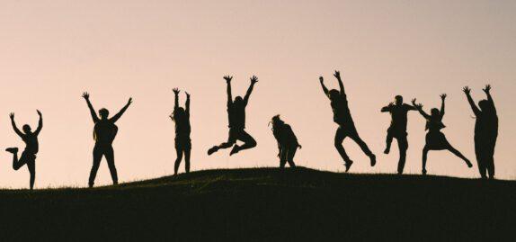 Joukko ihmisiä iloitsee mäen päällä kädet pystyssä.