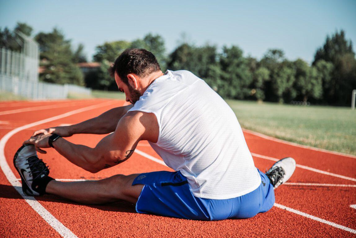 Kuvassa on maassa istuma urheilija venyttelemässä.
