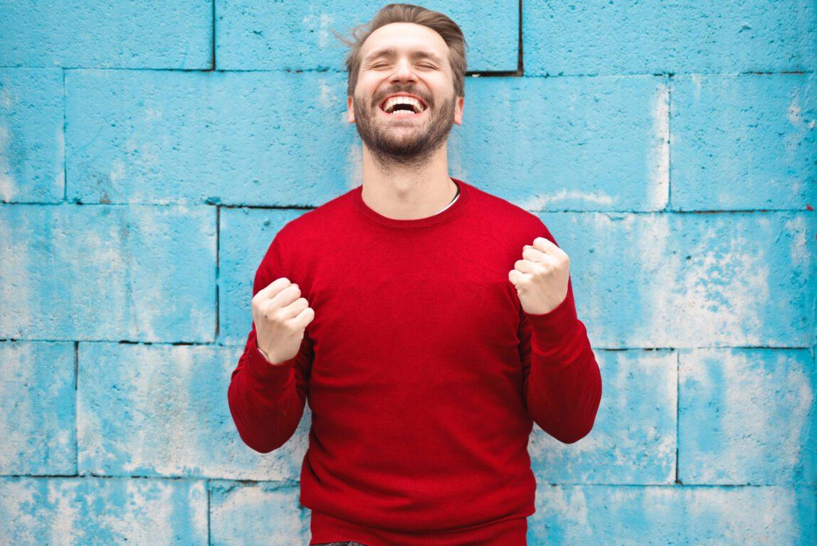 Kuvassa onnellisen näköinen mies pitää käsiä nyrkissä rintaansa vasten.