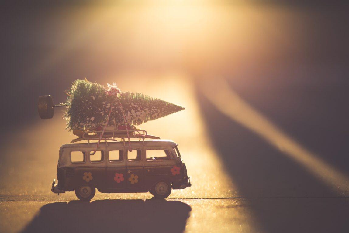 Kuvassa on auto, jonka katolla on joulukuusi.