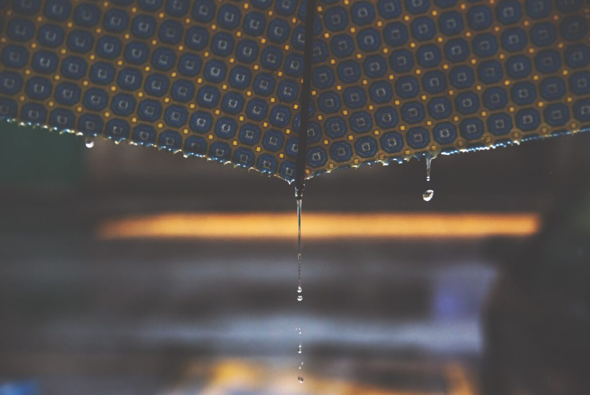 Kuvassa vesi tippuu sateenvarjon reunasta.