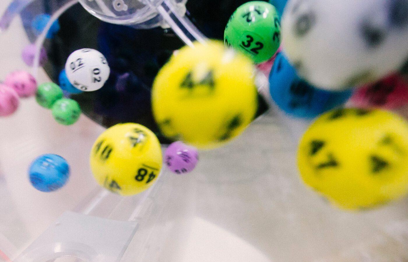 Kuvassa on erivärisiä lottopalloja, joissa on numeroita.