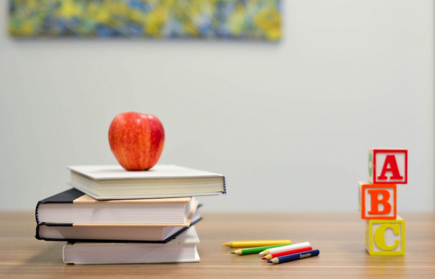 Kuvassa on pino kirjoja, joiden päällä on omena. Kuvassa on kyniä ja aakkospalikoita.