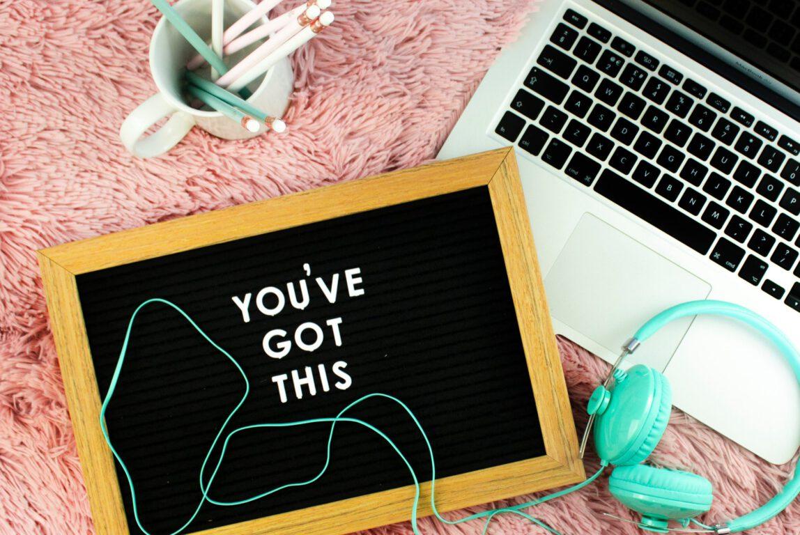 Kuvassa on tietokone, kuulokkeet ja taulu, jossa on teksti You've got this.