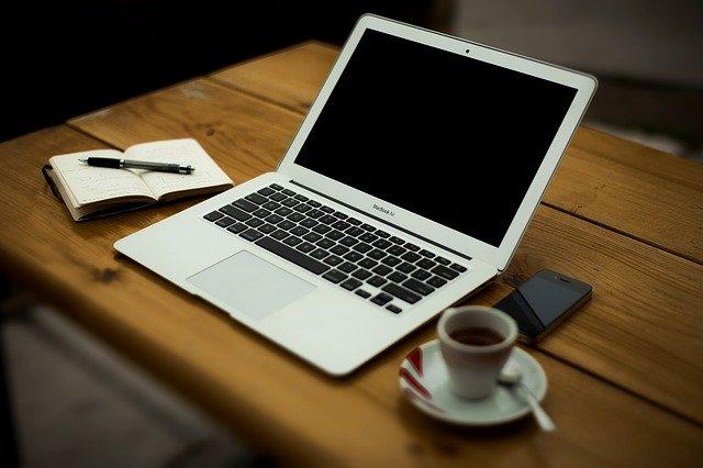 Lehtiö, kynä, kannettava tietokone, puheline ja kahvikuppi pöydällä