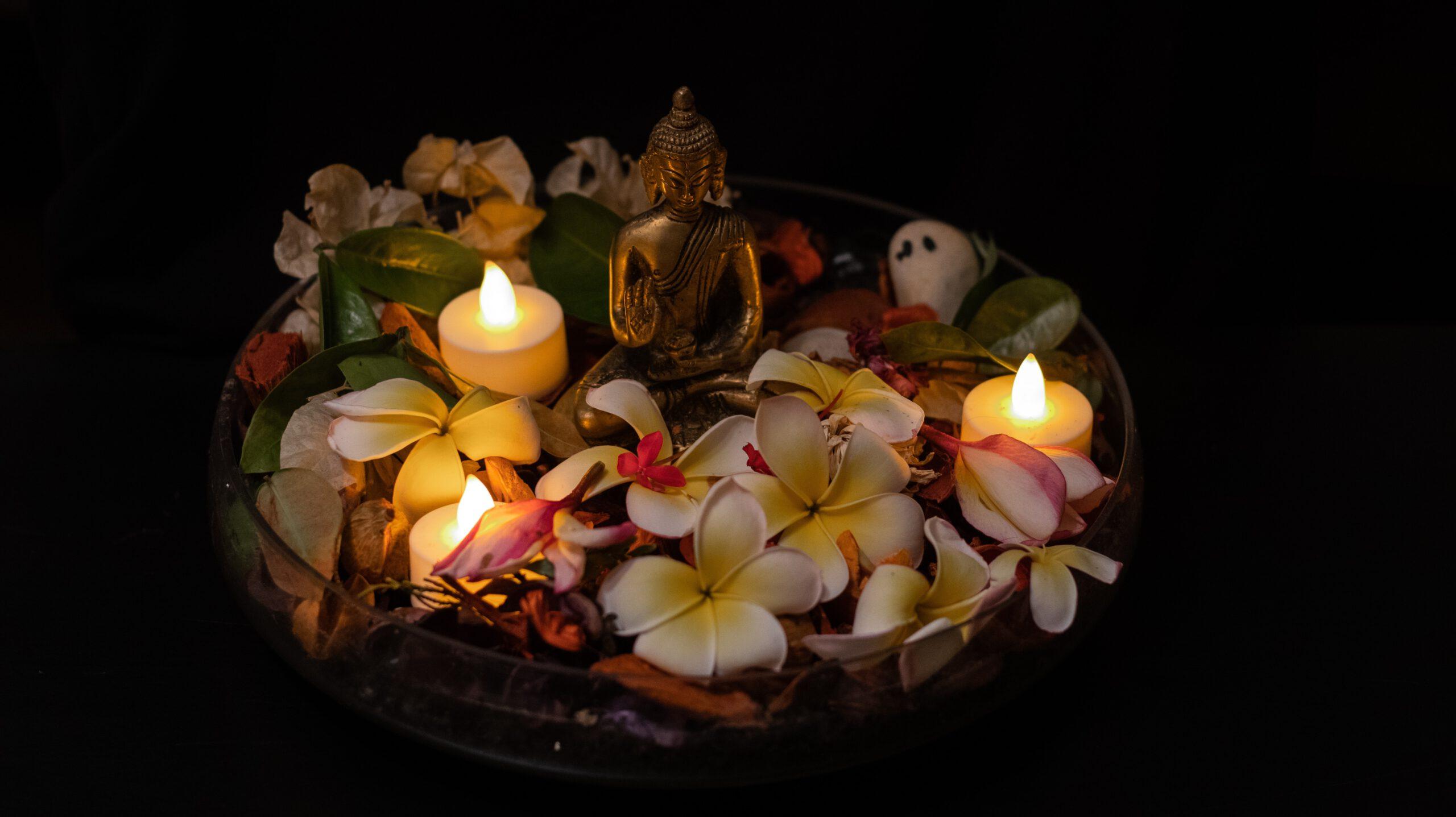 Meditoiva patsas, kynttilät ja kukkasia
