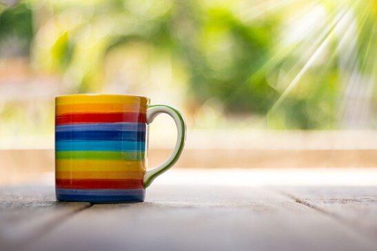 Sateenkaaren värinen kahvikuppi pöydällä auringon paisteessa.