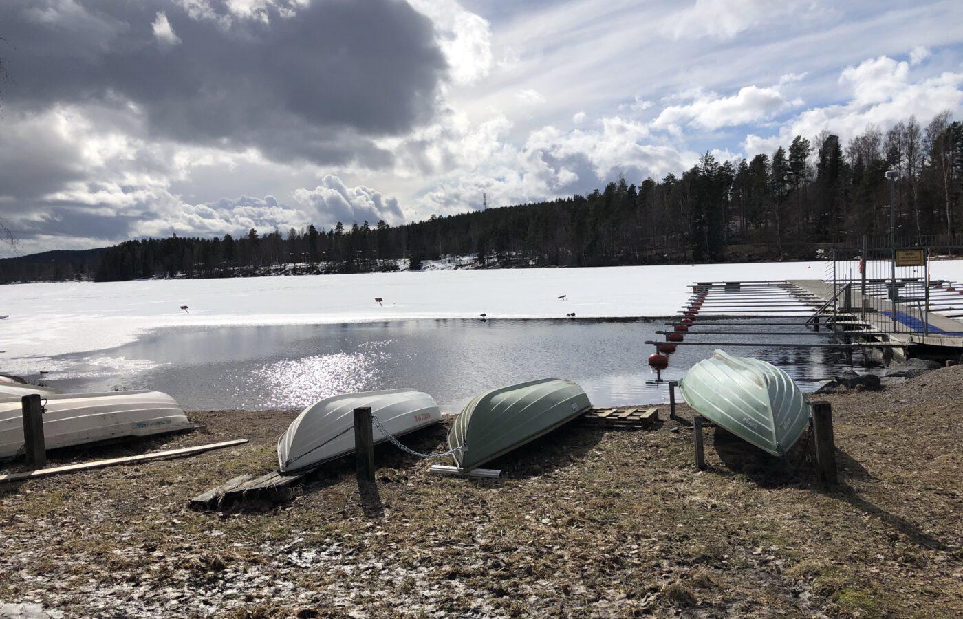 Kuvassa keväinen venelaituri, avanto ja veneitä talviteloilla.