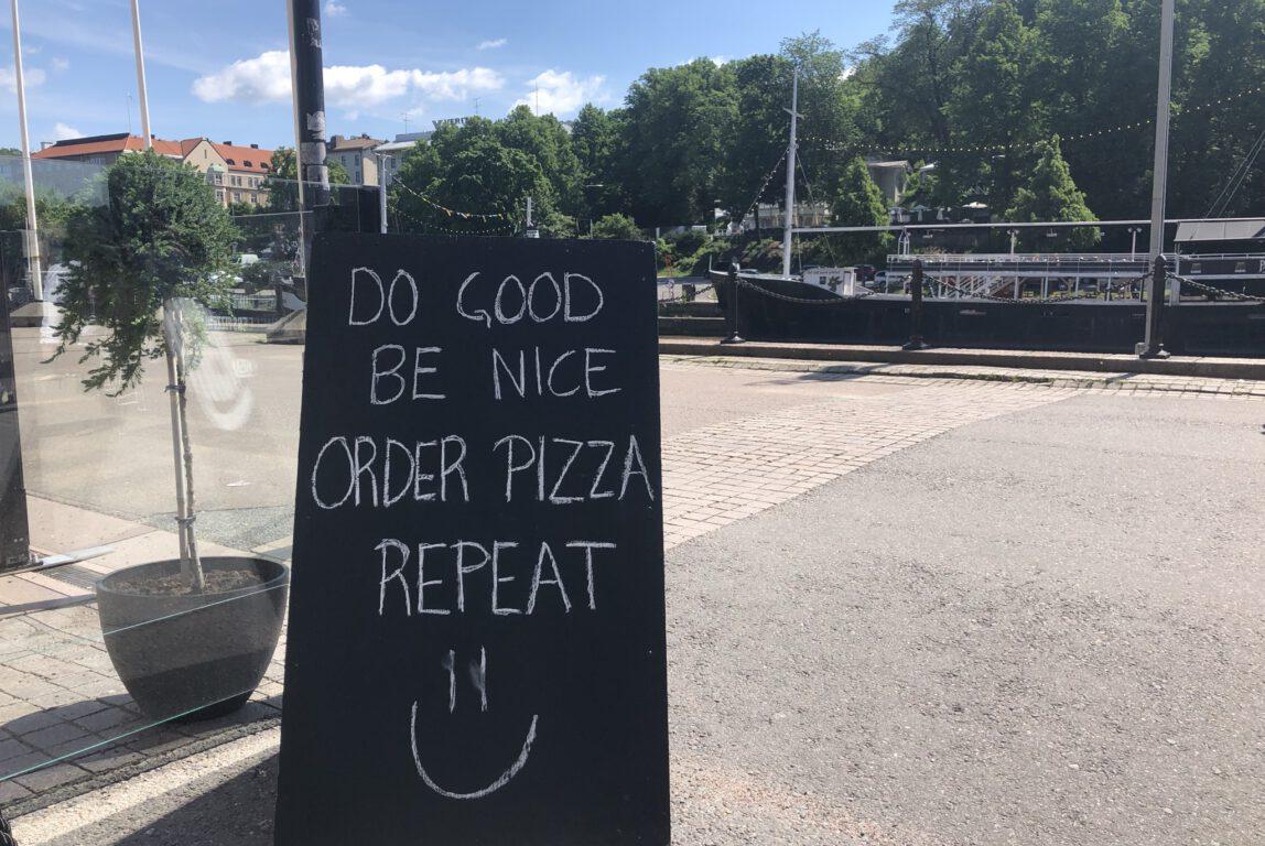 Kuvassa kesäisessä maisemassa musta mainoskyltti, jossa lukee valkoisilla kirjaimilla: do good, be nice, order pizza, repeat.
