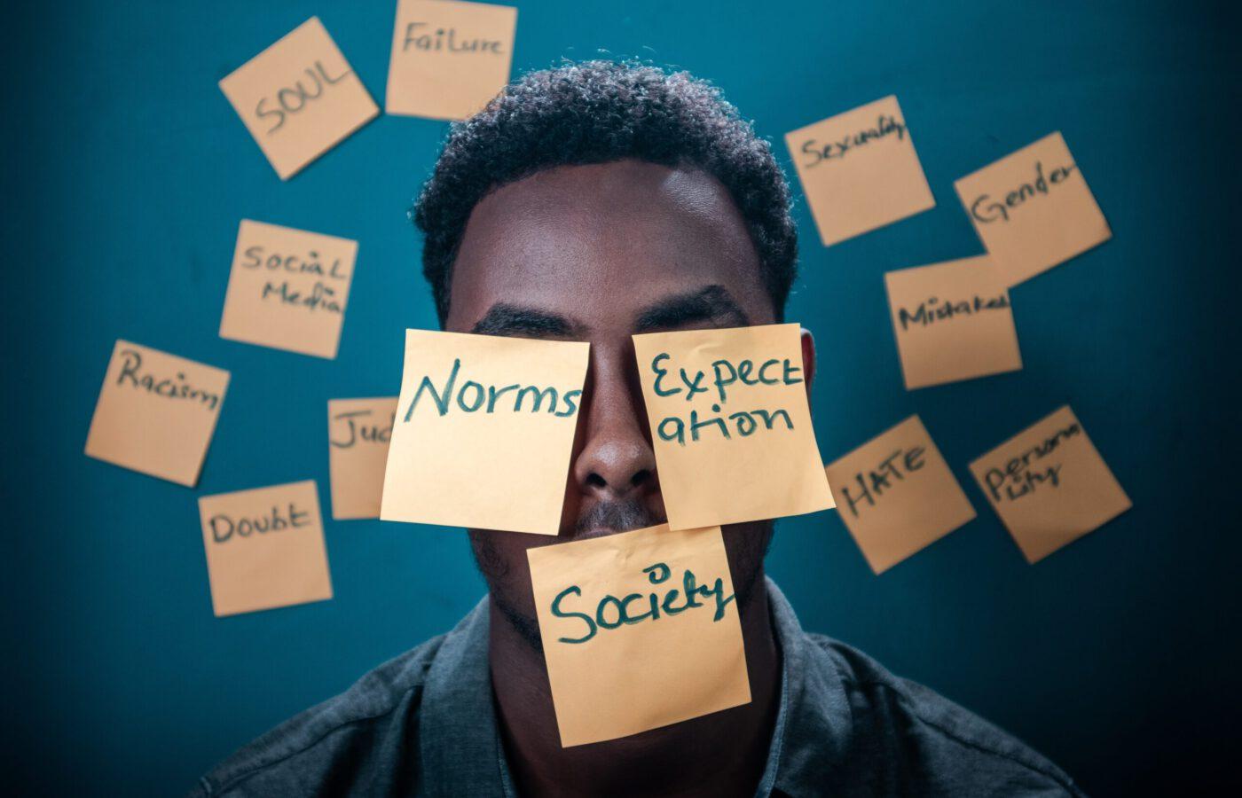 Kuvassa miesoletettu jonka kasvoilla ja ympärillä on muistilappuja, joihin on kirjoitettu normeja ja odotuksia kuvaavia sanoja.