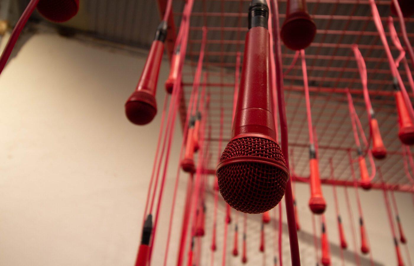 Kuvassa on katossa roikkuvia mikrofoneja, jotka symboloivat lausumista.