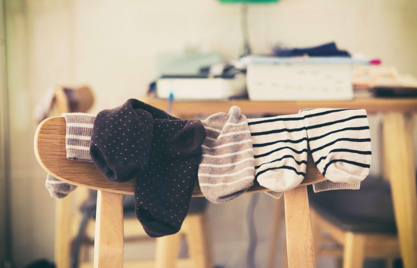 Kuvassa sukkia roikkumassa tuolin selkänojalla.