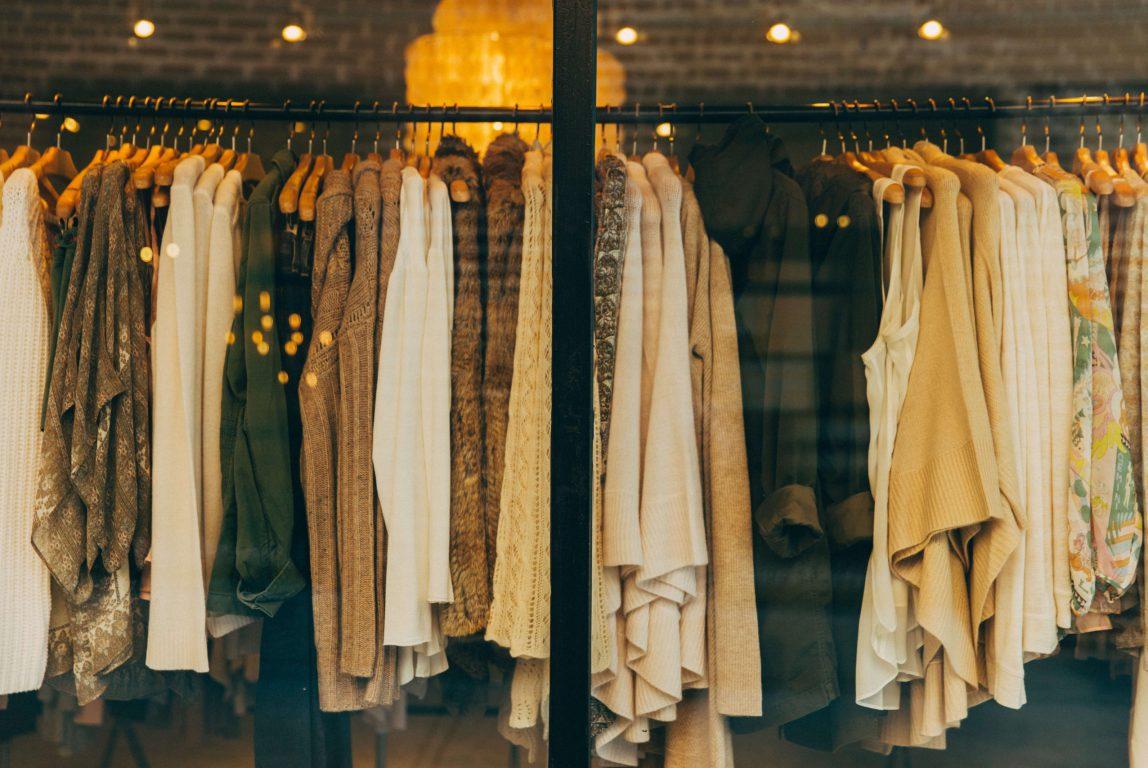 Vaatteita roikkumassa vaaterekissä näyteikkunassa.