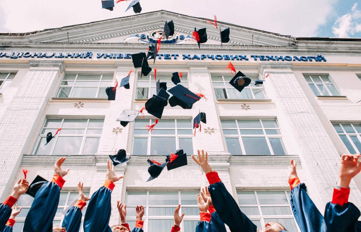 Kuvassa heitetään valmistujaislakkeja ilmaan koulun edessä.