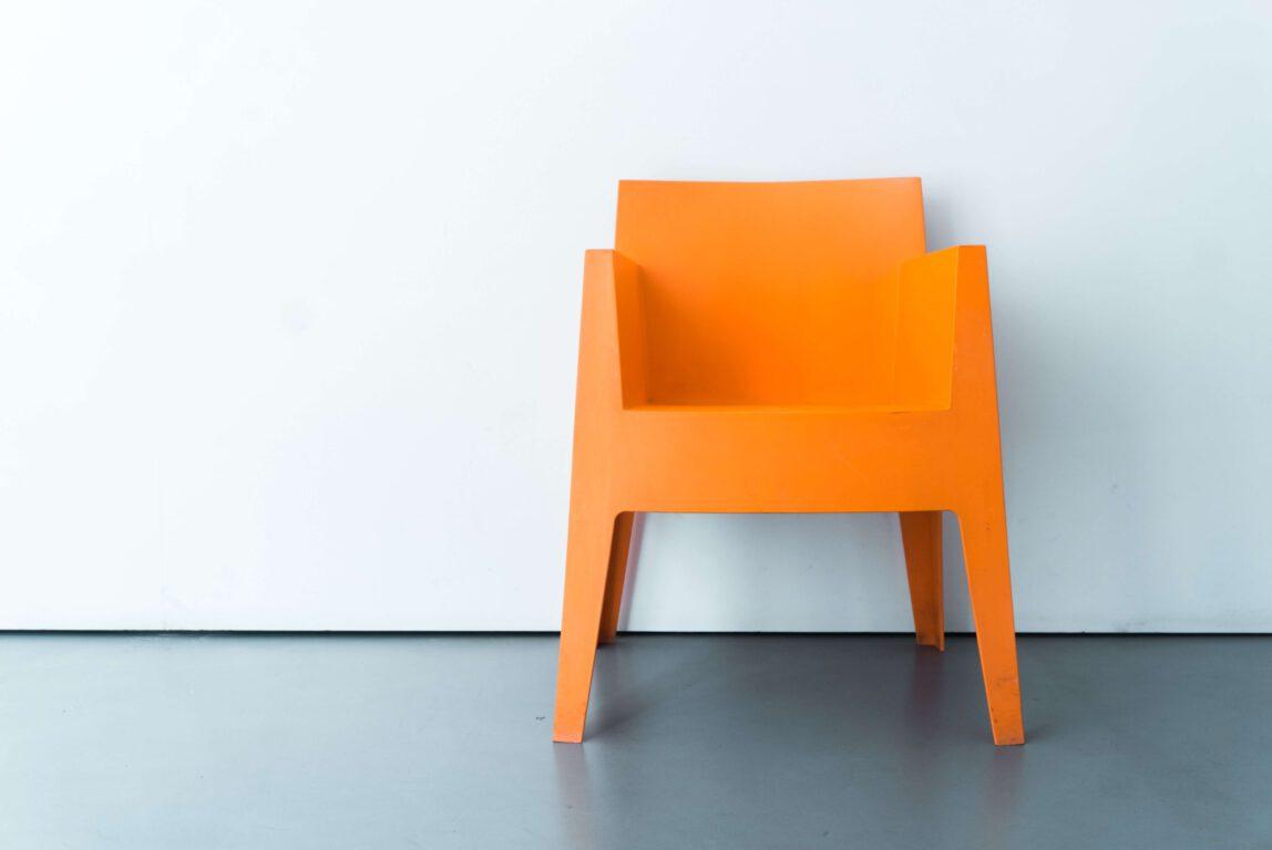 Oranssi tuoli seinän edessä