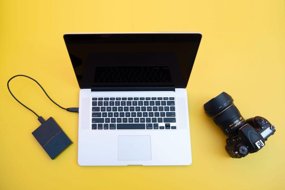 Kannettava tietokone ja järjestelmäkamera keltaisella pohjalla.