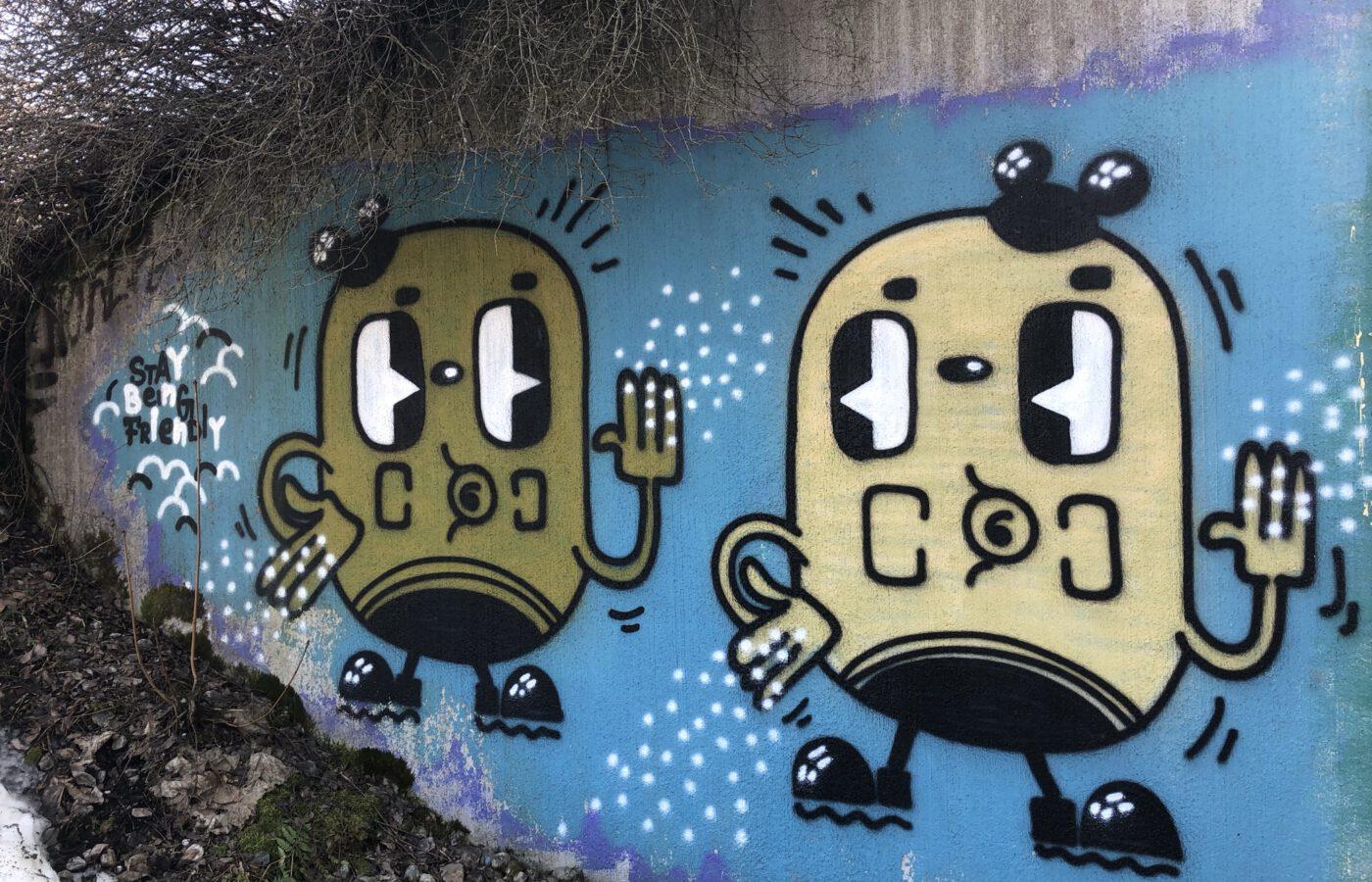 Kuvassa graffitikuva, jossa kaksi perunanmallista hahmoa heiluttelee toisilleen, kuva on koristeellinen.