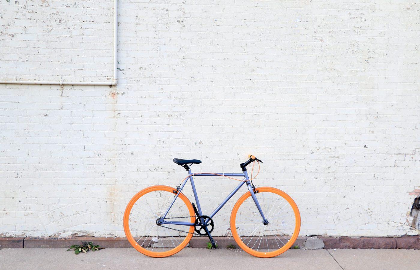 Kuvassa sininen polkupyörä nojaa harmaata seinää vasten.