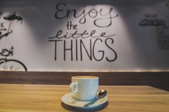 Valkoinen kahvikuppi pöydän päällä, takana seinällä lukee enjoy the little things.