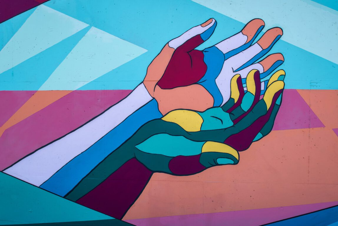 Kuvassa on kädet, jotka symboloivat koronavirusta viittauksella käsihygieniaan.