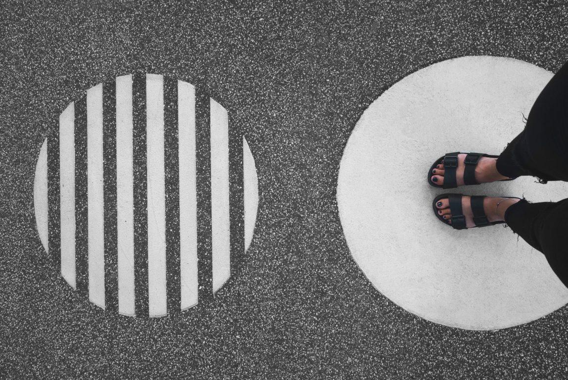 Mustavalkoisessa kuvassa on kaksi ympyrää. Toisessa ympyrässä näkyvät jalat sandaaleissa.