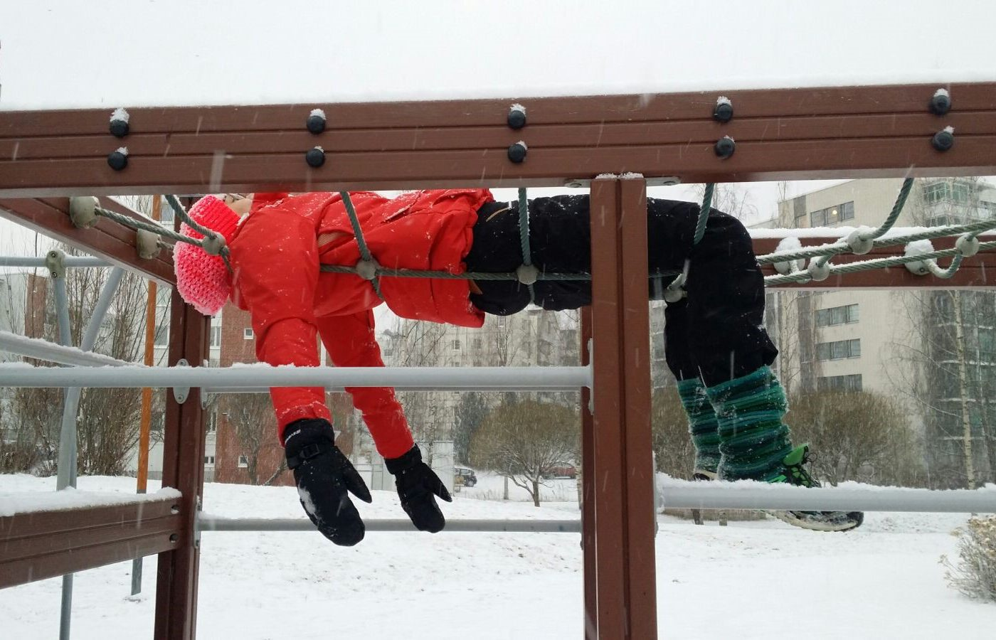 Kuvassa ihminen makaa selällään raajat roikkuen lasten kiipeilytelineessä lumisateessa.